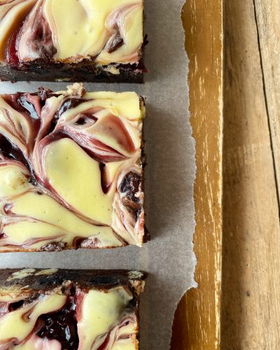 Black Forest brownie, white chocolate and cherry ripples running across top of brownie